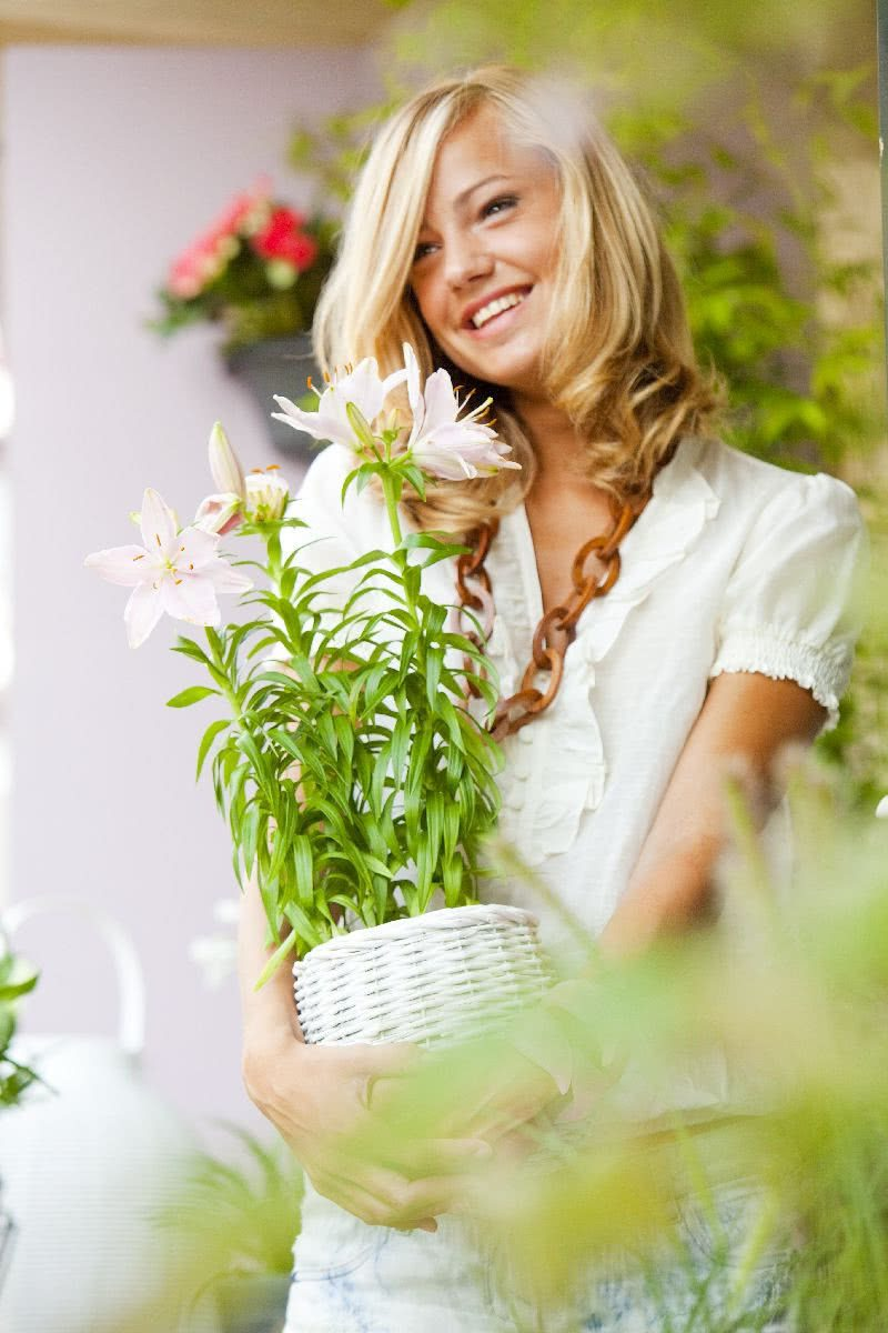 На фото женщина держит лилии в горшке